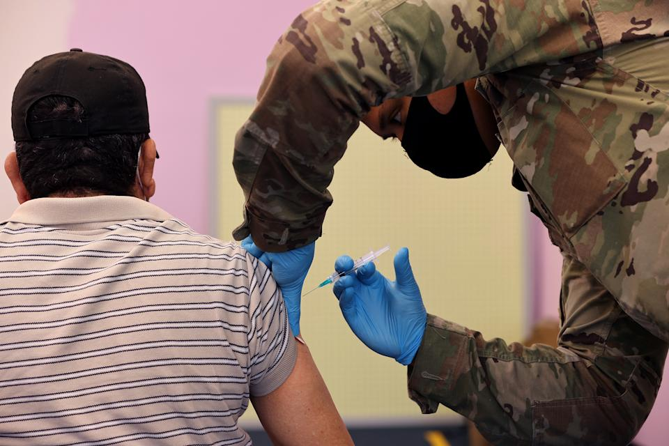 WHEATON, MARYLAND - MAY 21: Maryland National Guard Sgt. Jason Grant (R) administers a Moderna coronavirus vaccine at CASA de Maryland's Wheaton Welcome Center on May 21, 2021 in Wheaton, Maryland. The mobile vaccination clinic was staffed with members of the Maryland National Guard and part of the Maryland Vaccine Equity Task Force, which works with local health departments and community organizations to focus COVID-19 vaccination efforts on