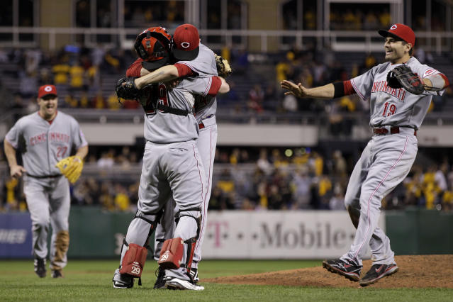Cincinnati Reds starting pitcher Homer Bailey hugs Cincinnati Reds catcher Ryan Hanigan, center, as first baseman Joey Votto (19) and third baseman Scott Rolen, left join the celebration after getting the final out of a no-hitter in a baseball game against the Pittsburgh Pirates in Pittsburgh Friday, Sept. 28, 2012. The Reds won 1-0. (AP Photo/Gene J. Puskar)