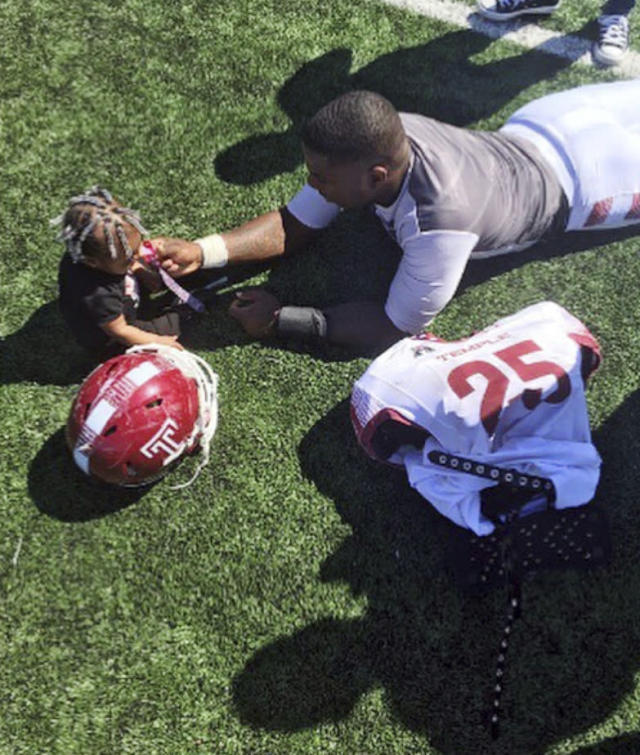 In this 2016 photo, Temple running back Ryquell Armstead plays on the field with his daughter Ry-kail during spring NCAA college football practice in Philadelphia. David Hood and Armstead shared a position and an apartment while playing for Temple. They also shared the experience of being fathers on top of students and football players. (Tara Armstead via AP)