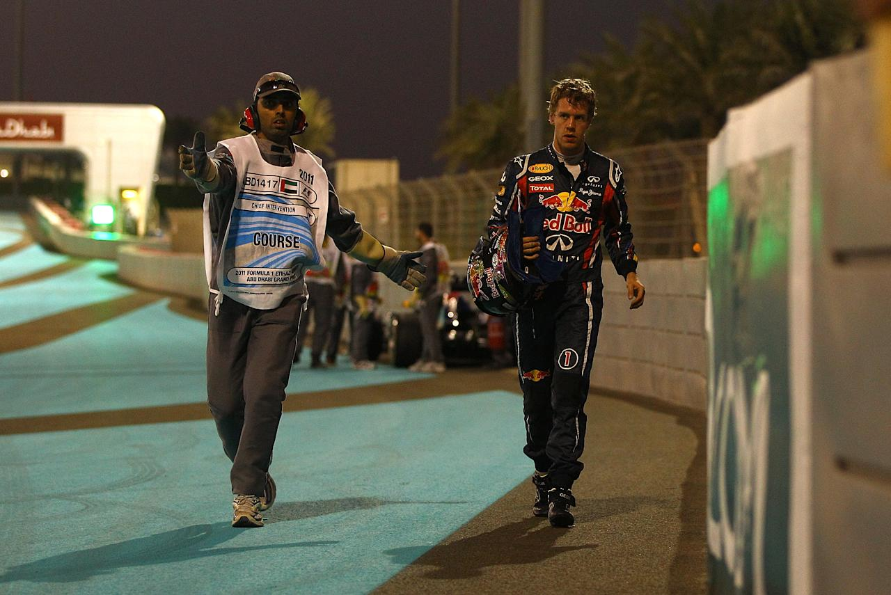 ABU DHABI, UNITED ARAB EMIRATES - NOVEMBER 12:  Sebastian Vettel of Germany and Red Bull Racing leaves his car on the track after crashing during practice ahead qualifying for the Formula One Grand Prix of Abu Dhabi at Yas Marina Circuit on November 12, 2011 in Abu Dhabi, United Arab Emirates.  (Photo by Vladimir Rys Photography/Getty Images)