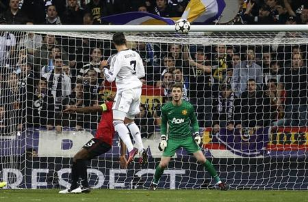 Real Madrid's Cristiano Ronaldo scores past Manchester United goalkeeper David De Gea (R) during their Champions League soccer match at Santiago Bernabeu stadium in Madrid February 13, 2013. REUTERS/Paul Hanna