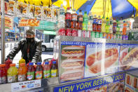 Mohammed Hussein works at his hot dog vending cart in New York's Times Square, Tuesday, April 27, 2021. In recent weeks, tourism indicators for New York City like hotel occupancy and museum attendance that had fallen off a pandemic cliff have ticked up slightly. It's a welcome sight for a city where the industry has been decimated by the impact of the coronavirus. (AP Photo/Mary Altaffer)