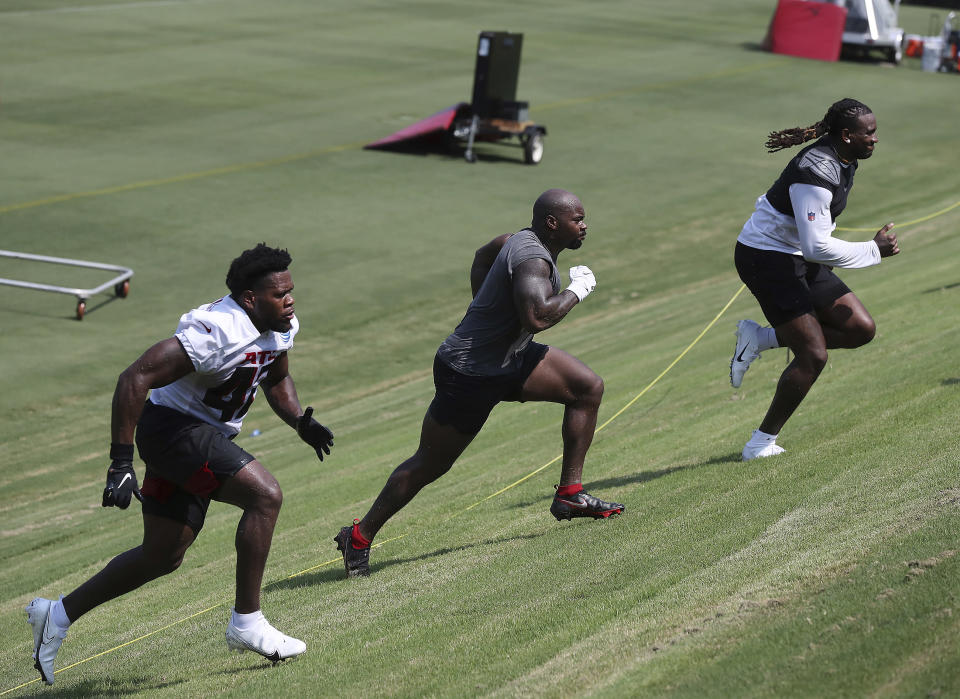 Atlanta Falcons linebacker Shareef Miller, left, and running backs Mike Davis, center, and Cordarrelle Patterson run the hill next to the practice fields at the team's NFL football training camp in Flowery Branch, Ga., Thursday, July 28, 2021. (Custis Compton/Atlanta Journal-Constitution via AP)