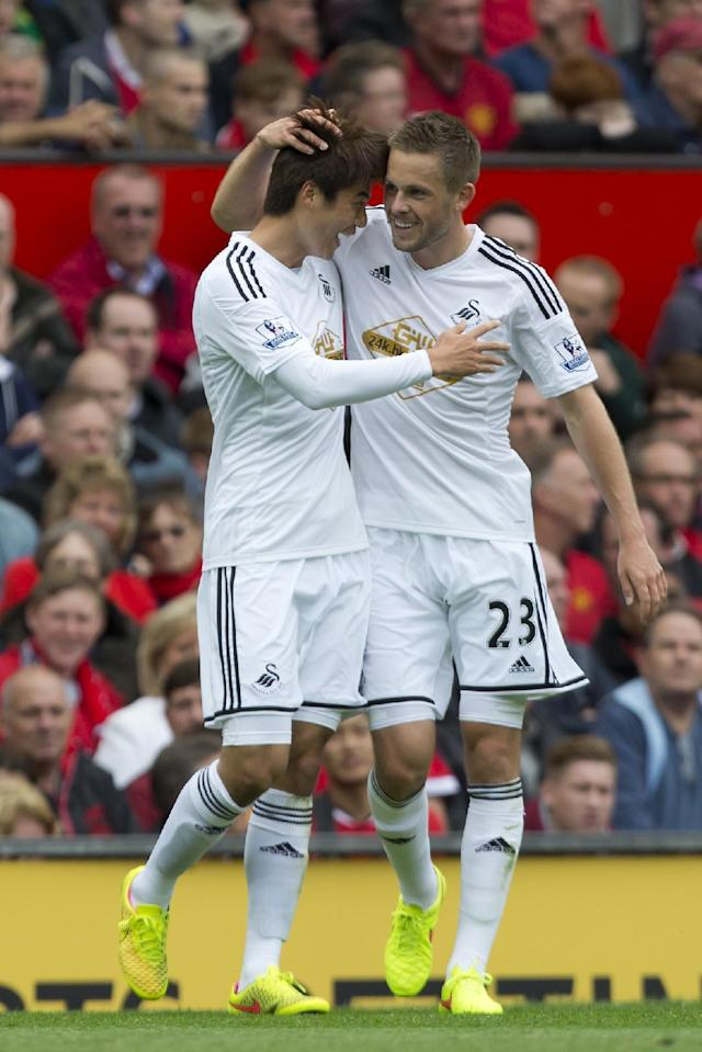 Swansea City's Ki Sung-Yeung, left, celebrates with teammate Gylvi Sigurdsson after scoring against Manchester United during their English Premier League soccer match at Old Trafford Stadium, Manchester, England, Saturday Aug. 16, 2014. (AP Photo/Jon Super)