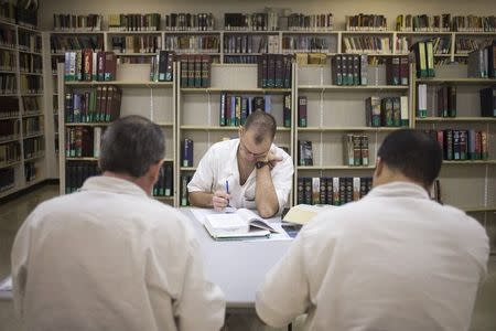 Offenders read and write papers inside the Southwestern Baptist Theological Seminary library located in the Darrington Unit of the Texas Department of Criminal Justice men's prison in Rosharon, Texas August 12, 2014. REUTERS/Adrees Latif