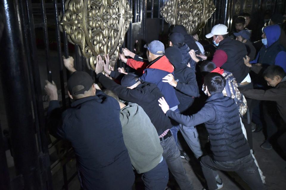 People try to storm the gate into the government headquarters during a rally against the results of a parliamentary vote in Bishkek, Kyrgyzstan, Monday, Oct. 5, 2020. Large crowds of people have gathered in the center of Kyrgyzstan's capital to protest against the results of a parliamentary election, early results of which gave the majority of seats to two parties with ties to the ruling elites amid allegations of vote buying. (AP Photo/Vladimir Voronin)