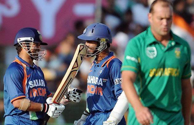 Indian cricketers Sachin Tendulkar (L) and Dinesh Karthik (C) share a light moment as South African captain Jacques Kallis walks to the right during the second One Day International (ODI) cricket match at the Captain Roop Singh Stadium in Gwalior on February 24, 2010. India are currently 198 runs for the loss of one wicket after thirty overs after electing to bat first. AFP PHOTO/ MANAN VATSYAYANA
