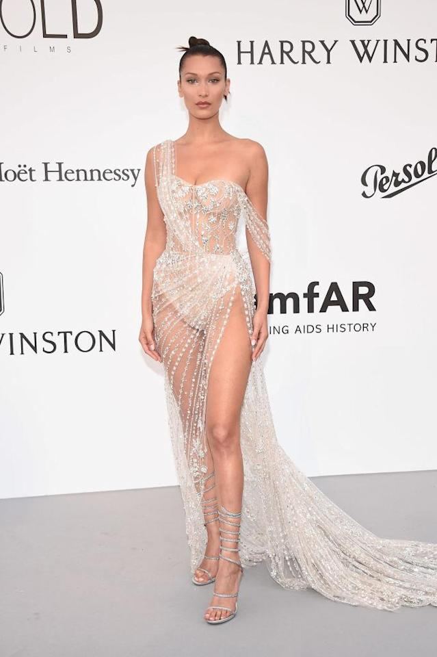 "<p>Bella Hadid wore a see-through Ralph & Russo gown that featured jewel embellishments to the 24th amfAR gala at the Hotel du Cap-Eden-Roc in Antibes on Thursday, May 25, 2017. ""I'm in heaven,"" she told <a href=""https://www.yahoo.com/style/glam-cannes-gala-bella-hadid-heaven-eva-longoria-finally-eat-122452403.html"" data-ylk=""slk:Yahoo"" class=""link rapid-noclick-resp"">Yahoo</a> Style at the gala. She also joked about her revealing gown, saying, ""We're going to see if it stays on me for the rest of the night. I'm going to hopefully make it through the red carpet, have no mishaps happen, and I'm happy.""<br>(Photo by Stephane Cardinale – Corbis/Corbis via Getty Images) </p>"