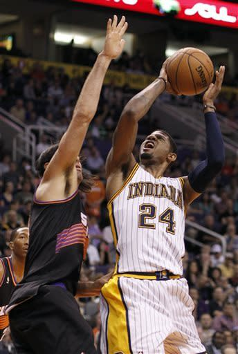Indiana Pacers forward Paul George, right, reacts after having been fouled by Phoenix Suns forward Luis Scola, left, of Argentina, during the first half of an NBA basketball game, Saturday, March 30, 21013, in Phoenix. (AP Photo/Paul Connors)