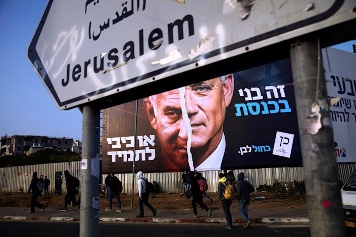 Palestinian laborers walk past an election campaign billboard