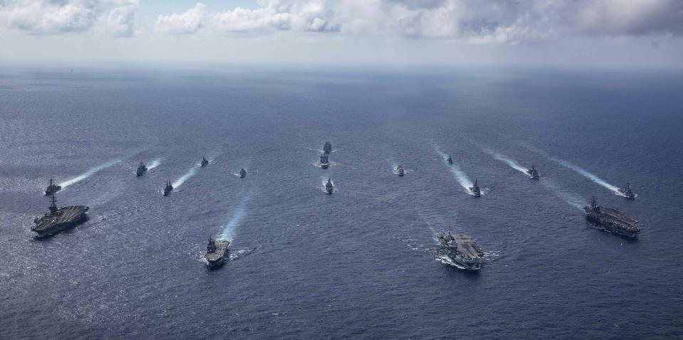 In this photo released by the U.S. Indo-Pacific Command, the United Kingdom's carrier strike group led by HMS Queen Elizabeth (R 08), and Japan Maritime Self-Defense Forces led by (JMSDF) Hyuga-class helicopter destroyer JS Ise (DDH 182) joined with U.S. Navy carrier strike groups led by flagships USS Ronald Reagan (CVN 76) and USS Carl Vinson (CVN 70) sails to conduct multiple carrier strike group operations in the Philippine Sea, on Oct. 3, 2021. After sending a record number of military aircraft to harass Taiwan over China's National Day holiday weekend, Beijing has toned down the sabre rattling but tensions remain high, with the rhetoric and reasoning behind the exercises unchanged. (Jason Tarleton/U.S. Navy via AP)