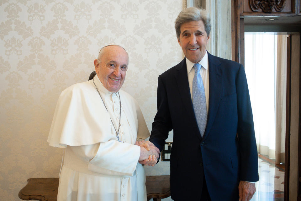 """Pope Francis and John Kerry, right, shake hands as they pose for a photo at the Vatican, Saturday, May 15, 2021. Former U.S. Secretary of State John Kerry, currently President Biden's envoy on the climate, met in private audience with Pope Francis on Saturday, afterward calling the pope """"a compelling moral authority on the subject of the climate crisis"""" who has been """"ahead of the curve."""" Kerry told Vatican News in an interview that the pope speaks with """"unique authority, compelling moral authority, that hopefull can push people to greater ambition to get the job done. (Vatican Media via AP)"""