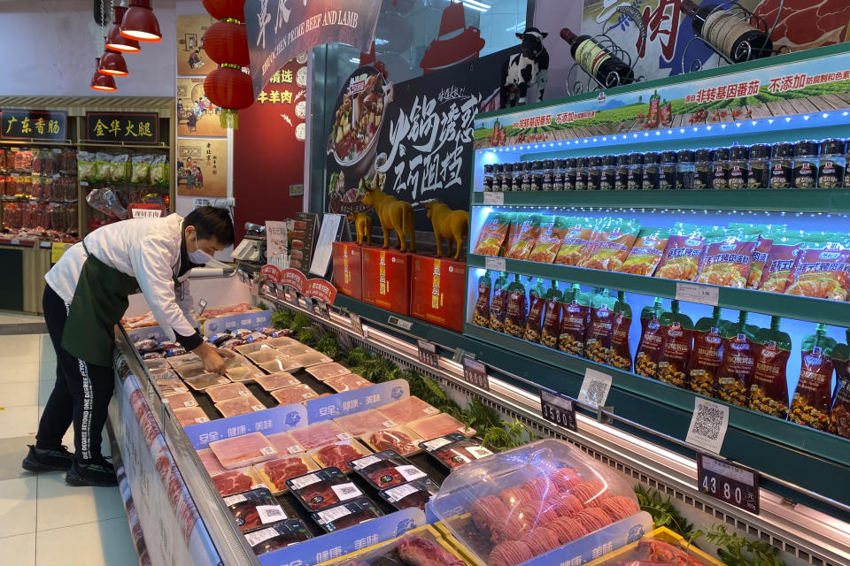 A worker wearing a mask handles meat products including beef from New Zealand packaged with a QR-code linked to its COVID test results at a supermarket in Beijing, Tuesday, Nov. 24, 2020. China has stirred controversy with claims it has detected the coronavirus on packages of imported frozen food. (AP Photo/Ng Han Guan)