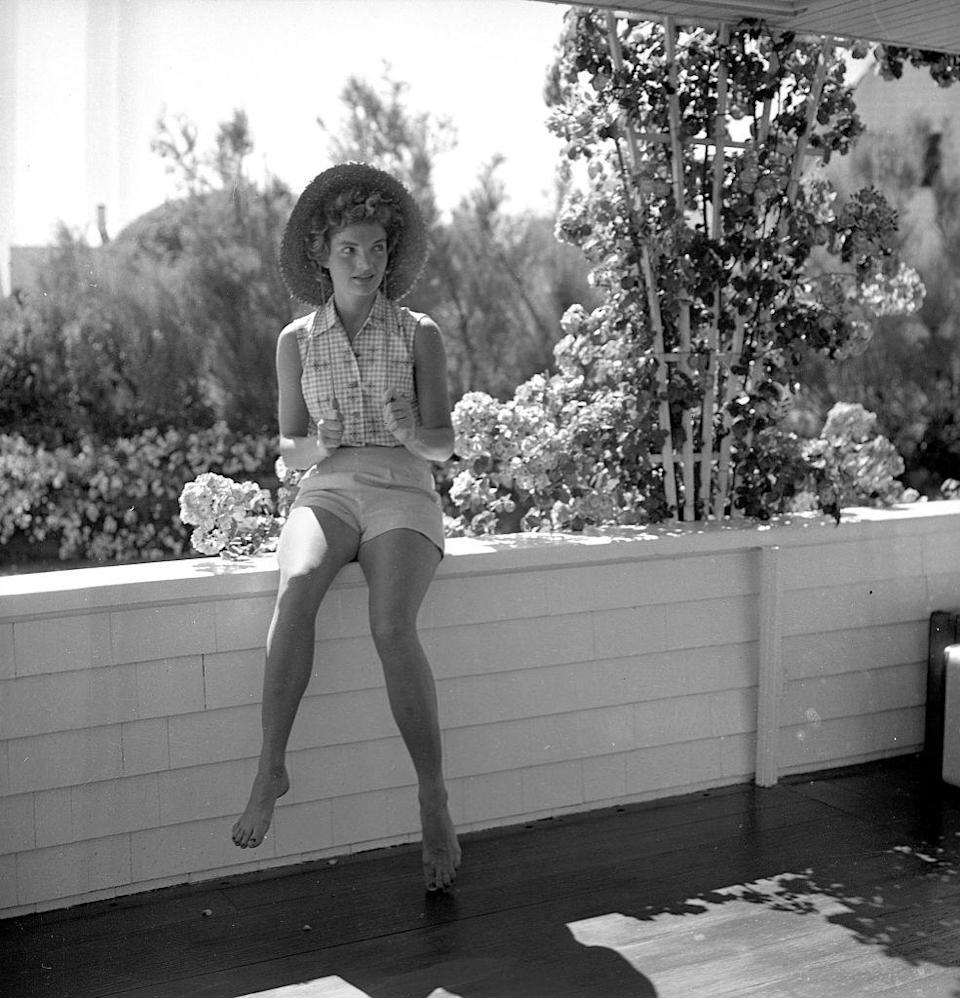 <p>Jackie sports a gingham button-down blouse and a straw hat—ever the picture of ease and graciousness—while vacationing at the Kennedy compound in Massachusetts.<br></p>