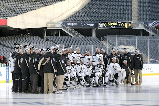 The Pittsburgh Penguins pose for a team photo on the Soldier Field ice, site of Saturday's Stadium Series NHL hockey game between the Penguins and the Chicago Blackhawks, Friday, Feb. 28, 2014, in Chicago. (AP Photo/Charles Rex Arbogast)