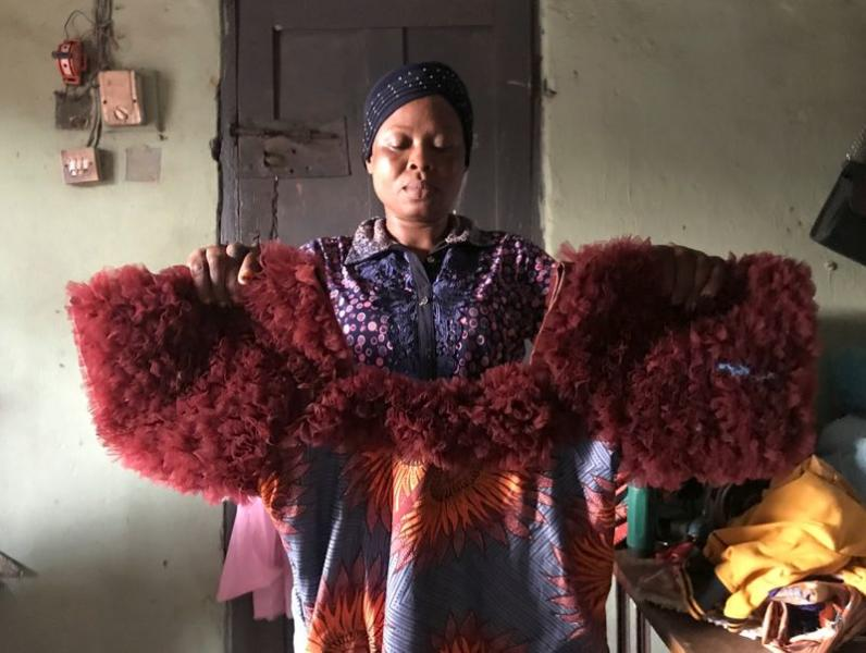 Kemi Adepoju, a dressmaker,  poses with a dress in her shop amid the spread of the coronavirus disease (COVID-19) in Lagos