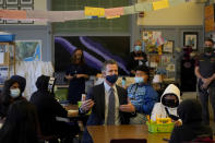 FILE — In this Oct. 1, 2021 file photo Gov. Gavin Newsom, middle, speaks to students in a seventh grade science class at James Denman Middle School in San Francisco. California schools have a few statewide requirements for how schools apply COVID rules for schools but leave most details up to the local districts, leading to a dizzying patchwork of approaches that parents and teachers say can be confusing and frustrating. (AP Photo/Jeff Chiu, File)