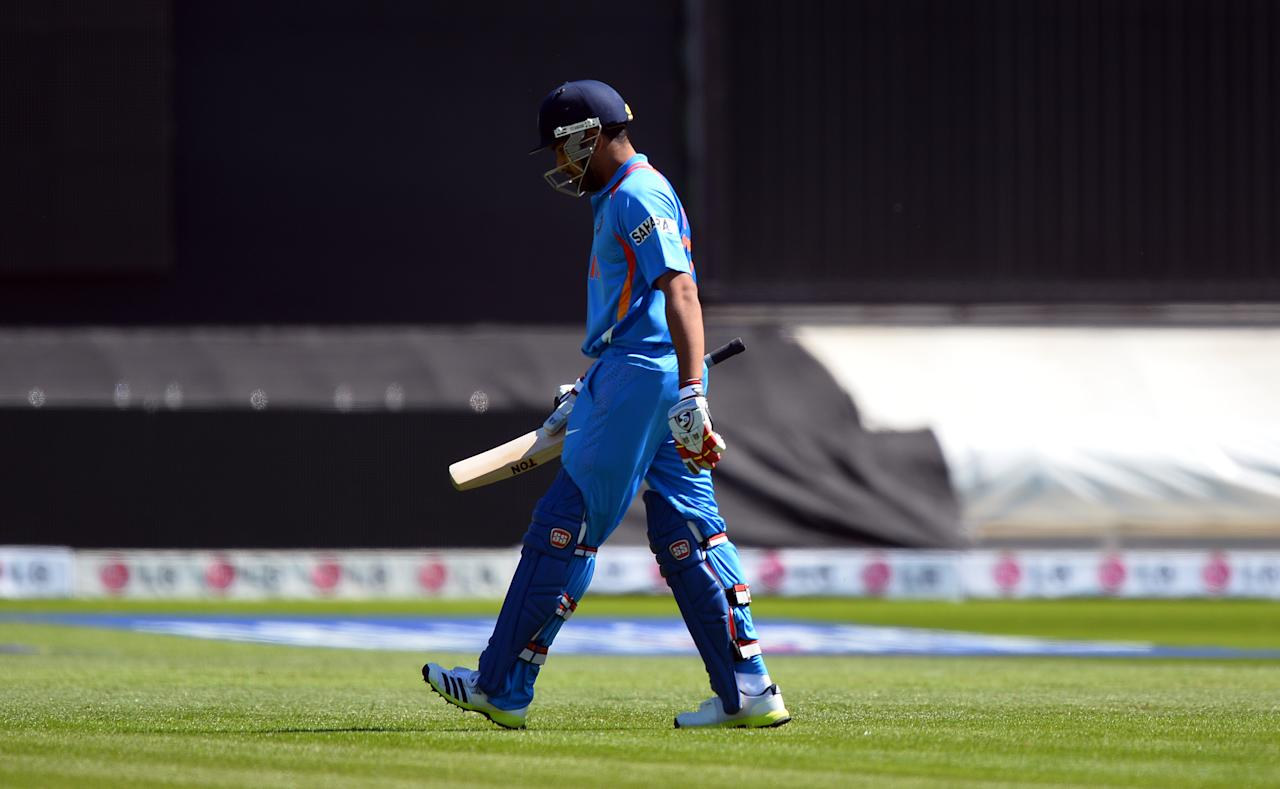 India's Rohit Sharma leaves the field during the warm-up cricket match ahead of the 2013 ICC Champions Trophy between India and Australia at The Cardiff Wales Stadium in Cardiff, Wales on June 4, 2013.  India won the toss and elected to bat first.  AFP PHOTO/Paul Ellis        (Photo credit should read PAUL ELLIS/AFP/Getty Images)