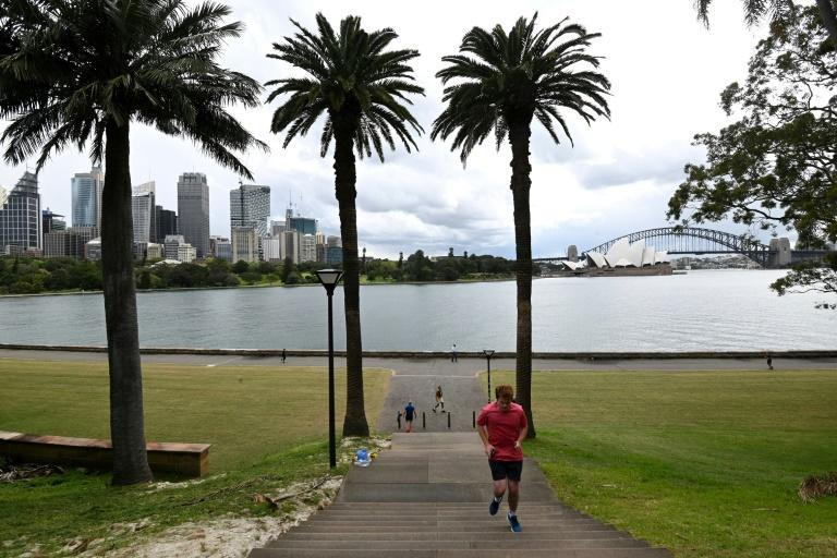 People exercise along Sydney Harbour as city dwellers enjoy a slight easing of lockdown rules (AFP/Saeed KHAN)