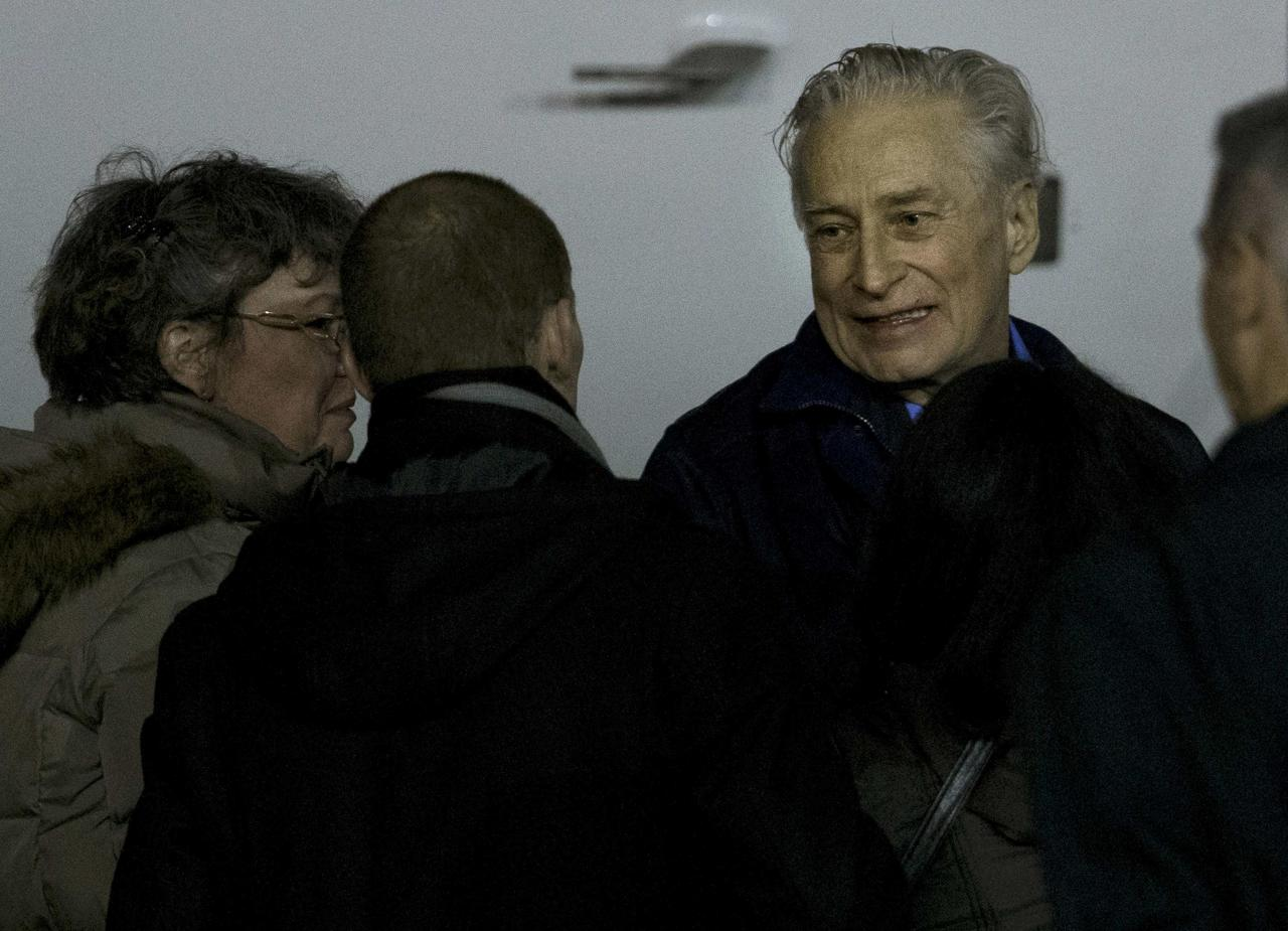 Former French hostage Francis Collomp is welcomed by relatives and officials on the tarmac upon his arrival at Villacoublay military airport, near Paris, November 18, 2013. Collomp, a French engineer who had been held hostage by Islamist militants in northern Nigeria for almost a year, has escaped his jailers, France's president said on Sunday. REUTERS/Kenzo Tribouillard/Pool (FRANCE - Tags: POLITICS)