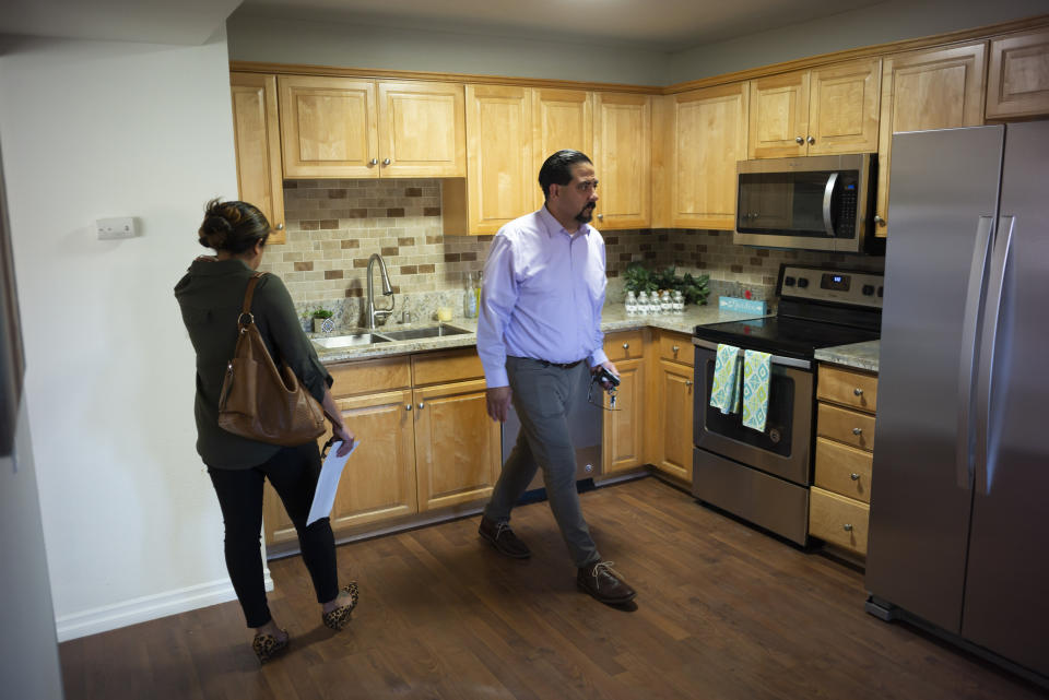 In this June 20, 2019 image, Irene Scully, left, talks with real estate agent Fred Portillo Sr., as they tour an apartment for rent in Escondido, Calif. Despite a decade of economic growth, wealth has become more exclusive in the United States, as fewer middle-class Americans own homes or have a stake in the stock market than they did before the Great Recession. (AP Photo/Gregory Bull)
