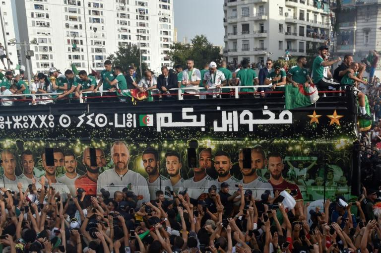 Algeria's national team players greet fans lining the streets during an open-top bus parade in the capital Algiers following their Africa Cup triumph