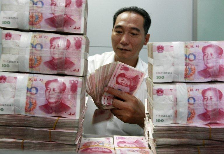 A Chinese bank staff member counts stacks of 100-yuan n in Huaibei, east China's Anhui province on August 17, 2012