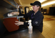 As the cases of Coronavirus spiral upward, Eileen Krause cleans condiment dispensers on the main concourse of Pepsi Center before an NHL hockey game between the New York Rangers and Colorado Avalanche Wednesday, March 11, 2020, in Denver. (AP Photo/David Zalubowski)