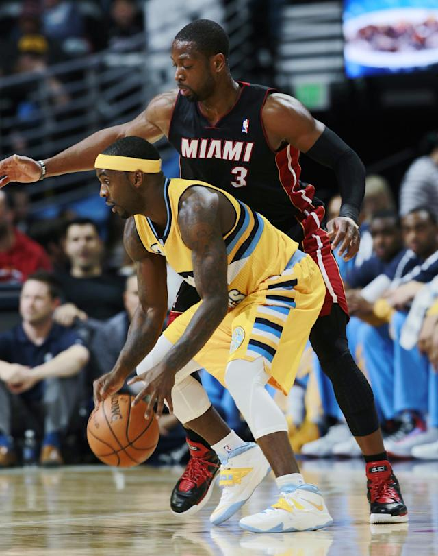 Denver Nuggets guard Ty Lawson, front, is covered by Miami Heat guard Dwyane Wade in the first quarter of an NBA basketball game in Denver on Monday, Dec. 30, 2013. (AP Photo/David Zalubowski)