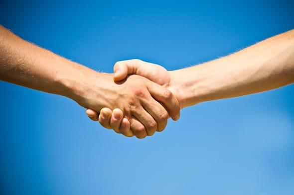 shaking hands of two business...