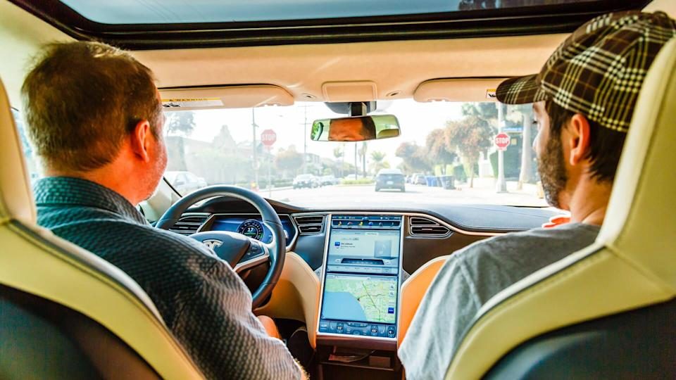 Los Angeles, United States - May 17, 2013: Men driving in electric car Tesla Model S on street of Santa Barbara in Los Angeles, California, USA.