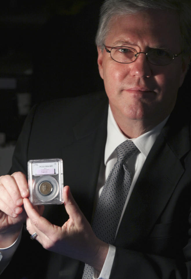 In this Thursday, April 19, 2012, photo, Todd Imhof, executive vice-president of Heritage Auction Galleries in Dallas poses for a photo with a copper and silver 1792 experimental penny that was put up for auction in Schaumburg, Ill. Officials with Heritage Auctions say Kevin Lipton of Beverly Hills, Calif., bought the penny on behalf of a group of unnamed investors for $1 million and must also pay the auction house's 15 percent commission. It was never actually put into circulation and only 14 examples of the coin are known to exist. (AP Photo/Daily Herald, George LeClaire) MANDATORY CREDIT; MAGS OUT; TV OUT