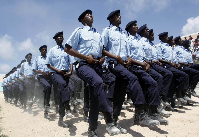 """FILE - In this July 1, 2013, file photo, Somali policemen march during the Somalia's Independence Day, at Konis stadium in Mogadishu, marking 53 years since the Southern regions of Somalia gained independence from Italy and joined with the Northern region of Somaliland to create Somalia. Twenty years after the U.S. military's """"Black Hawk Down"""" disaster, the Obama administration is slowly stepping up relations with Somalia even though security requires American officials to be sheltered behind blast walls and unable to see nearly any of the chaotic country. (AP Photo/Farah Abdi Warsameh, File)"""