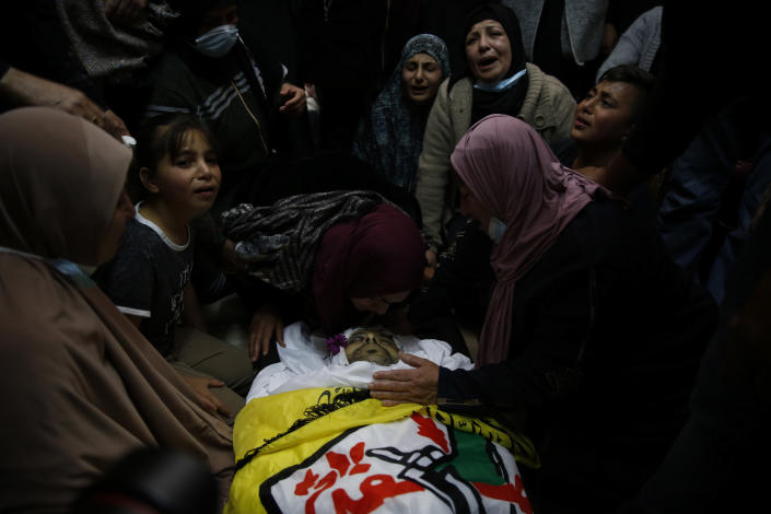 Palestinians mourn by the body of Osama Mansour during his funeral, in the village of Biddu near the West Bank city of Ramallah, Tuesday, April 6, 2021. Mansour was killed by Israel soldiers at a temporary vehicle checkpoint in the occupied West Bank near Jerusalem. The military said the soldiers thwarted an attempted car-ramming attack in the village of Bir Nabala. But the man's wife, who was in the car with him and was wounded by the gunfire, said the couple followed the soldiers' instructions and posed no threat. (AP Photo/Majdi Mohammed)