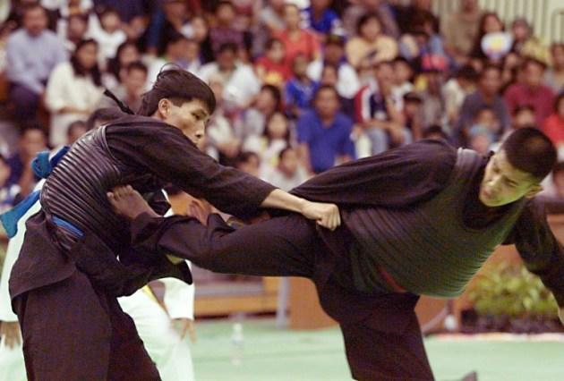Abdul Kadir (R) of Singapore lands a kick on Phu Sau Bui (L) of Vietnam to score a point in the mens' Pencak Silat 65-70 kg Wiralaga combat event at the 20th Southeast Asian Games in Bandar Seri Begawan 13 August 1999. The Singaporean fitness instructor won the gold despite a small injury during the fight. AFP PHOTO/ROMEO GACAD