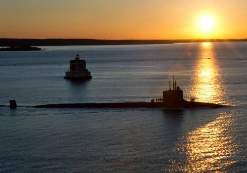 A Virginia-class submarine sales in front of the sunset.