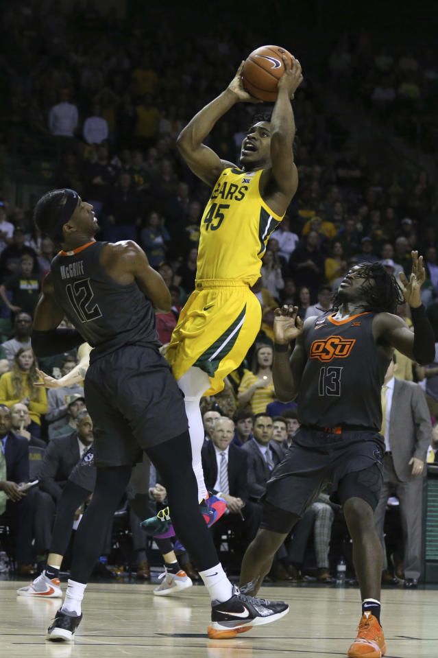 Baylor guard Davion Mitchell shoots over Oklahoma State forward Cameron McGriff, left, and guard Isaac Likekele, right, during the second half of an NCAA college basketball game Saturday, Feb. 8, 2020, in Waco, Texas. (AP Photo/Rod Aydelotte)