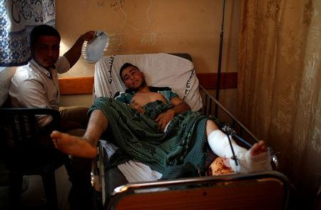 A man cools off an injured Palestinian as he lies on a bed at a hospital in Gaza City May 15, 2018. REUTERS/Mohammed Salem