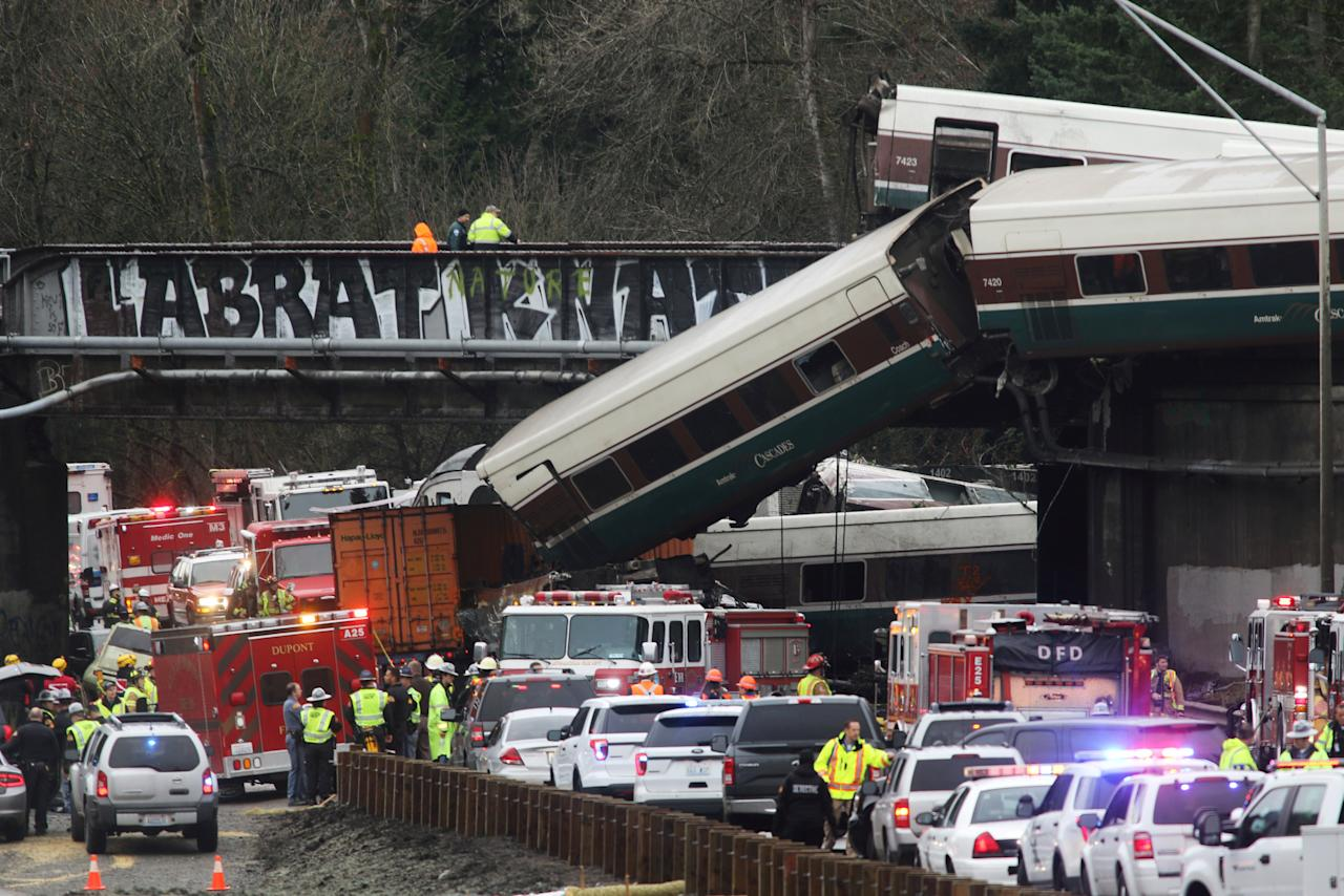 First responders are at the scene of an Amtrak passenger train which derailed and is hanging from a bridge over the interstate highway (I-5) in DuPont, Washington, U.S., December 18, 2017.    REUTERS/Nick Adams     TPX IMAGES OF THE DAY