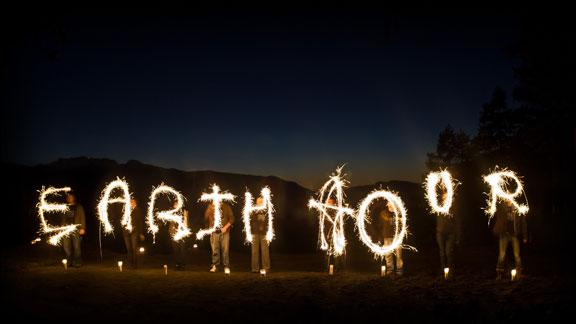 A group of people spelling out Earth Hour with sparklers against a dark sky on Vancouver Island, Earth Hour 2010, Canada