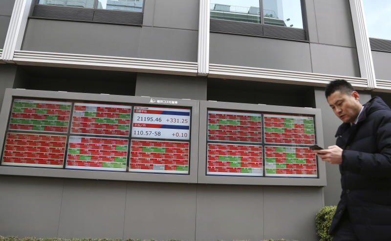 A man walks by an electronic stock board of a securities firm in Tokyo, Wednesday, Feb. 13, 2019. Asian shares were mostly higher Wednesday, cheered by prospects for a resolution to the costly trade dispute between the U.S. and China, which had also sent Wall Street indexes higher. (AP Photo/Koji Sasahara)