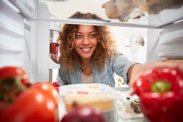 View Looking Out From Inside Of Refrigerator As Woman Opens Door And Unpacks Shopping Bag Of Food