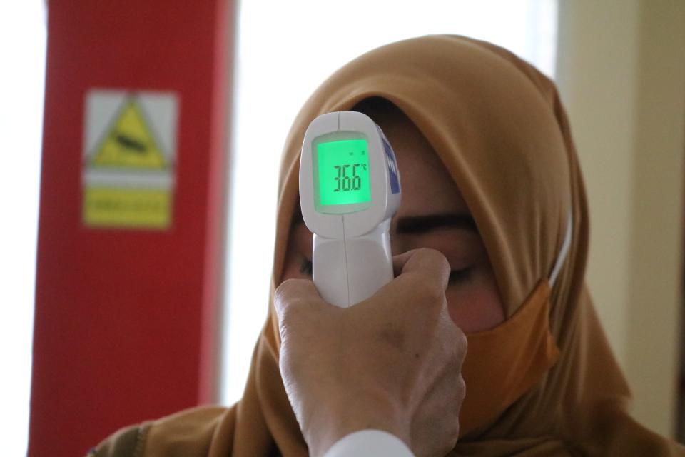 A woman in a hijab gets her temperature taken.
