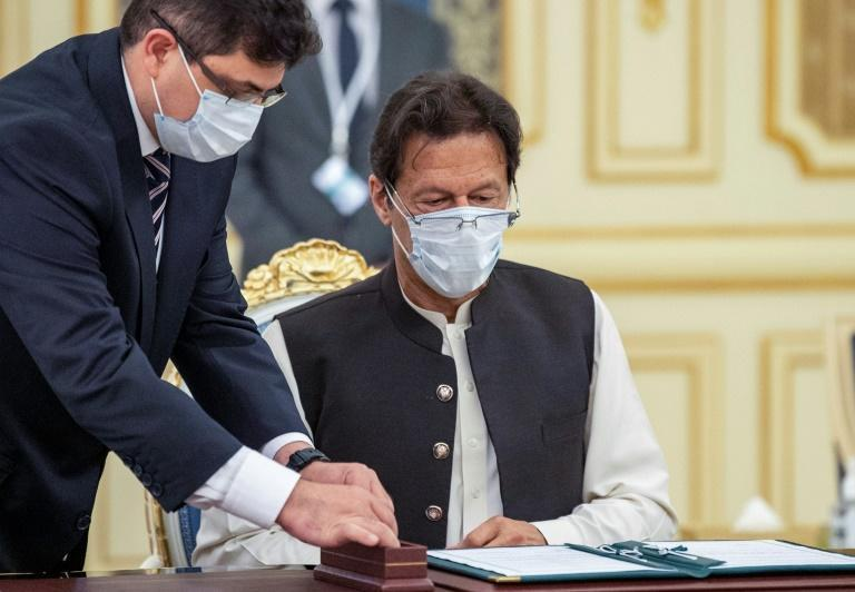 Pakistani Prime Minister Imran Khan prepares to sign one of a number of agreements he signed with his Saudi host