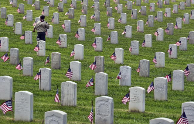 <p>A Boy Scout runs between the grave stones after helping place flags at the Los Angeles National Cemetery on Saturday, May 26, 2018. Thousands of scouts have placed American flags on the graves of veterans in a ceremony ahead of Memorial Day. More than 6,000 children participated in the event. Each uniformed scout placed a flag in the ground by each grave and saluted. Organizers say nearly 90,000 flags were placed in tribute. (Photo: Richard Vogel/AP) </p>