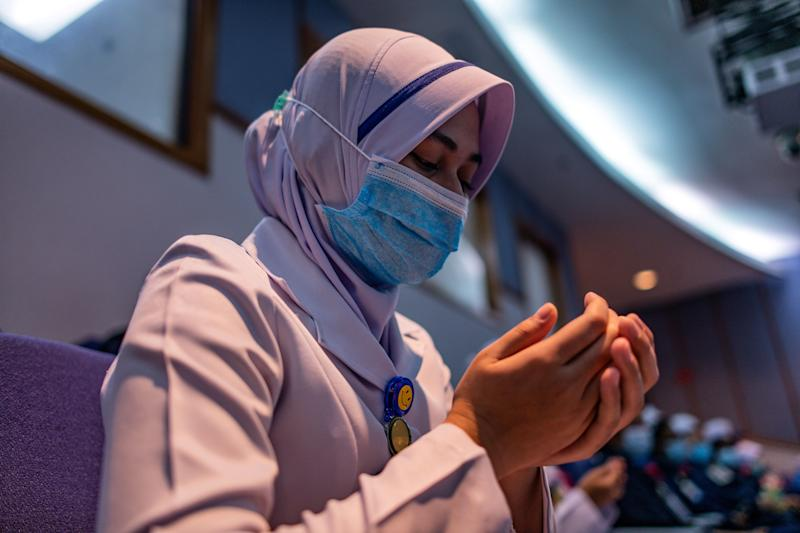 A staff nurse, wearing a face mask as a preventive measure against the spread of the COVID-19 novel coronavirus, offers prayers during a ceremony to commemorate International Nurses Day at the Selayang Hospital in Selayang on May 12, 2020. - As frontline hospital staff are constantly facing the risks from the COVID-19 coronavirus outbreak, the world is marking International Nurses Day, celebrated around the world every May 12, the anniversary of Florence Nightingale's birth. (Photo by Mohd RASFAN / AFP) (Photo by MOHD RASFAN/AFP via Getty Images)