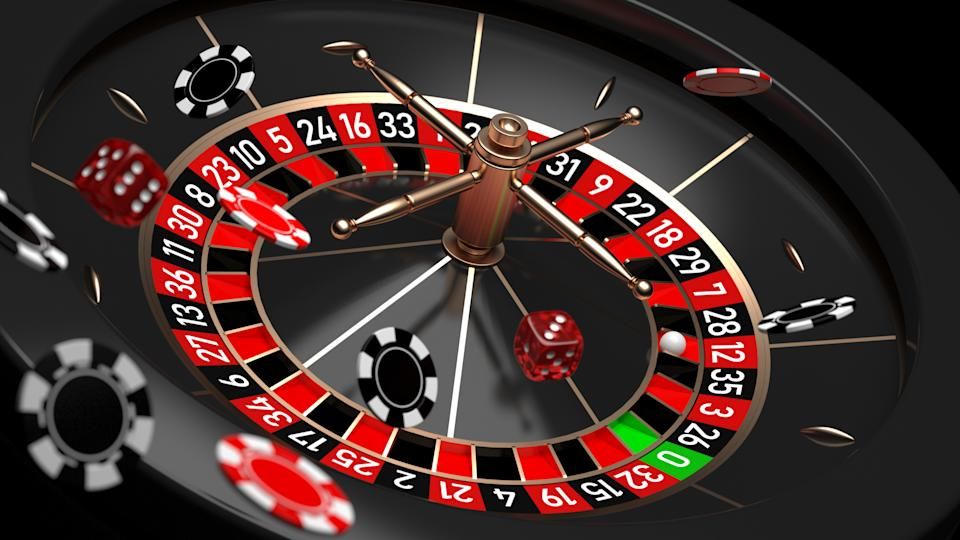 Roulette wheel with flying casino chips and dice. (Photo: Getty Images)