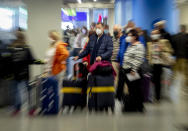 Passengers queue for a flight at the airport in Frankfurt, Germany, Saturday, Nov. 7, 2020. (AP Photo/Michael Probst)