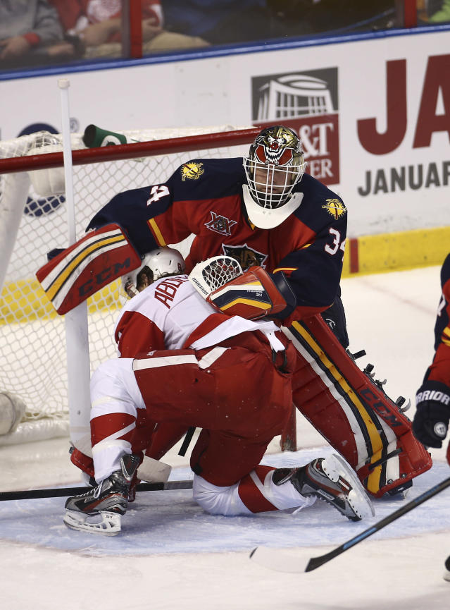 Detroit Red Wings' Justin Abdelkader (8) slides into Florida Panthers goalie Tim Thomas (34) during the second period of a NHL hockey game in Sunrise, Fla., Tuesday, Dec. 10, 2013. (AP Photo/J Pat Carter)