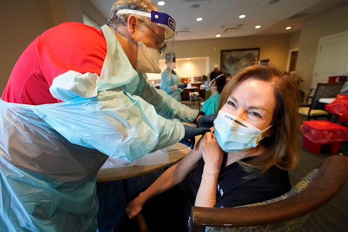 Health care worker Pam Peter, right, prepares to receive her second dose of COVID-19 vaccine last month in Pompano Beach, Fla. Medical workers and long-term care patients and staff were at the front of the line for inoculations.